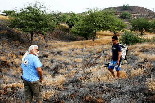 During a tour of the new public access walking trail, Kailapa homesteader Maha Kanealiʻi (in blue) stops to talk to a local fisherman using the Ala Loa Trail to holoholo.